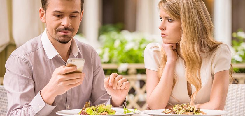 Man kijkt geboeid naar zijn smartphone terwijl zijn tafelgenote geërgerd toekijkt.